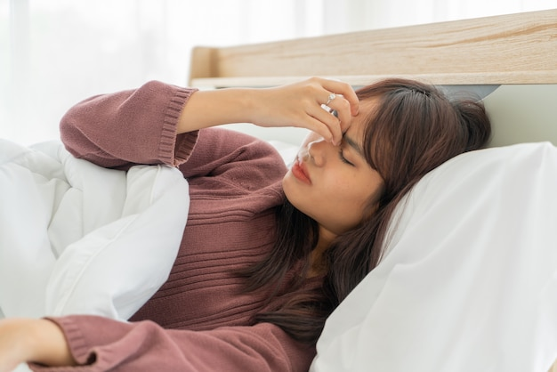 Asian woman headache and sleeping on bed Premium Photo