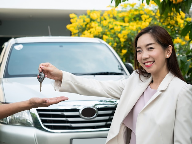 Asian woman holding car key to a man.  car driving, traveling trip, vehicle automobile rent, safety insurance Premium Photo