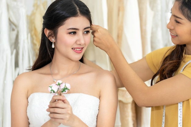 Asian woman holding flower measuring on wedding dress in a shop by the tailor. Premium Photo