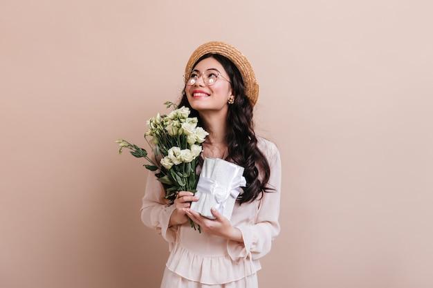 花とプレゼントを持っているアジアの女性。ベージュで分離されたトルコギキョウの花束を持つインスピレーションを得た日本人女性のスタジオショット。 無料写真