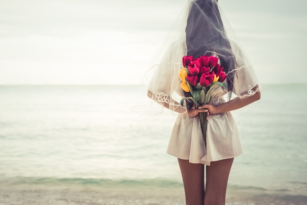 Asian Woman Holding Flowers In Behind And Waiting For Someone Make