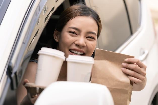 Азиатская женщина, держащая мешок еды от привода через ресторан Premium Фотографии