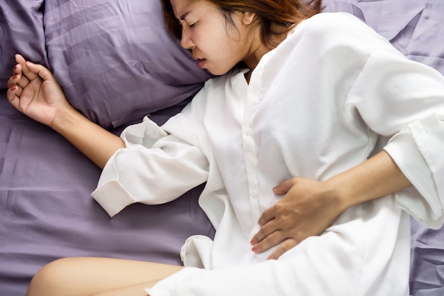 Asian woman holding left side of stomach pain in bed Premium Photo