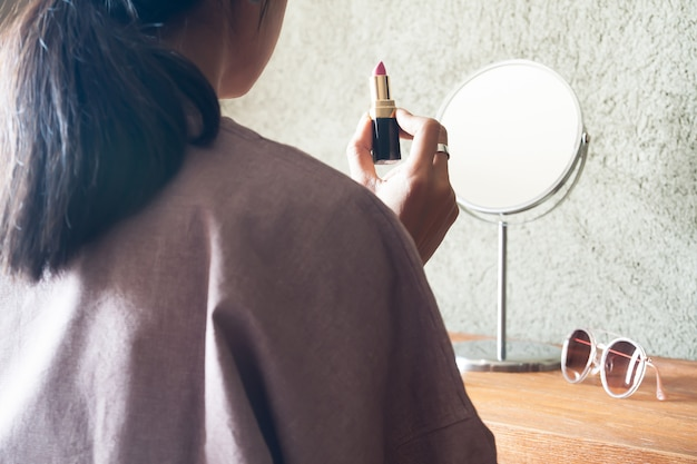 Asian woman holding lipstick preparing makeup to go out. beauty and lifestyle concept Premium Photo