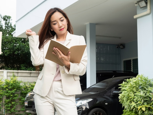 Asian woman holding notebook while standing in front of house. Premium Photo