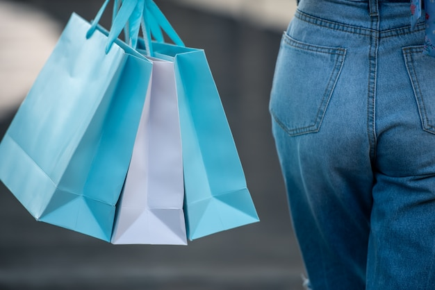 Asian woman holding shopping bags at mall Premium Photo