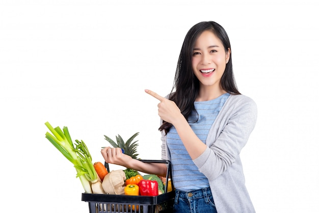 Asian woman holding shopping basket full of vegetables and groceries Premium Photo