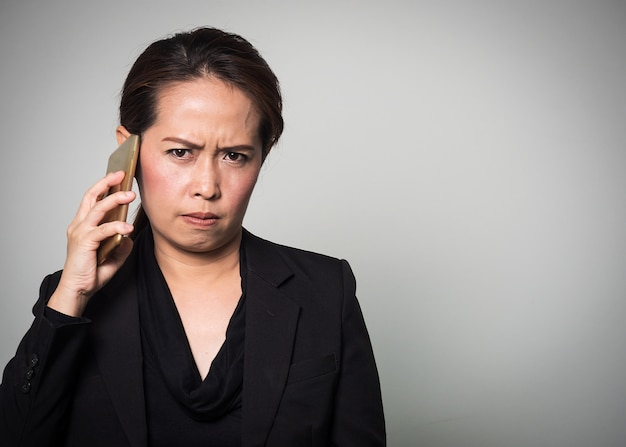 Asian woman holding smart phone in angry and boring emotion. Premium Photo