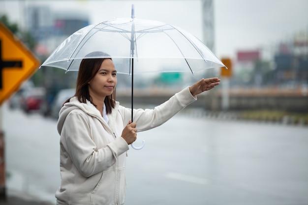 Азиатская женщина, держащая зонтик, автостоп, такси на городской улице в дождливый день. Premium Фотографии