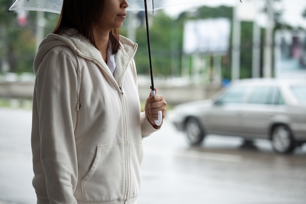 Азиатская женщина, держащая зонтик во время ожидания такси и стоя на тротуаре города в дождливый день. Premium Фотографии