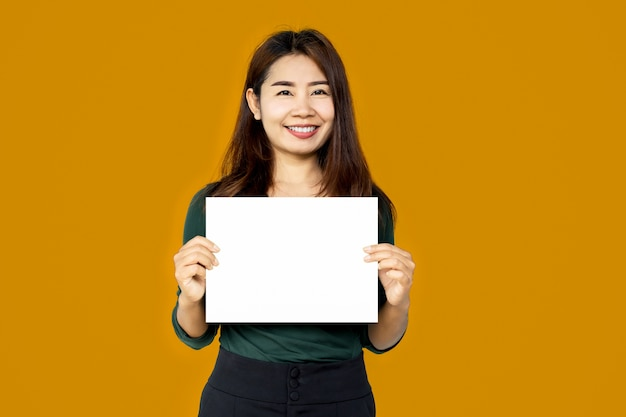 Asian woman holding white paper sheet over yellow background Premium Photo