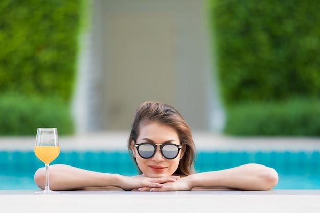 オレンジジュースのガラスとプールでアジアの女性 Premium写真