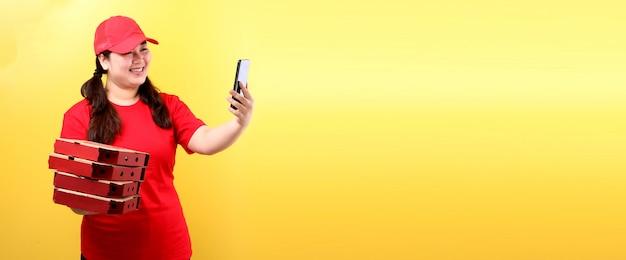 赤い帽子のアジアの女性は、空白の白い空の画面で携帯電話を保持している分離された段ボール箱に食品注文イタリアのピザを与えます。 Premium写真