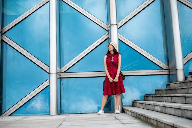 モダンな建物で赤いドレスを着たアジアの女性、都会のライフスタイルを持つ女性の女の子 Premium写真