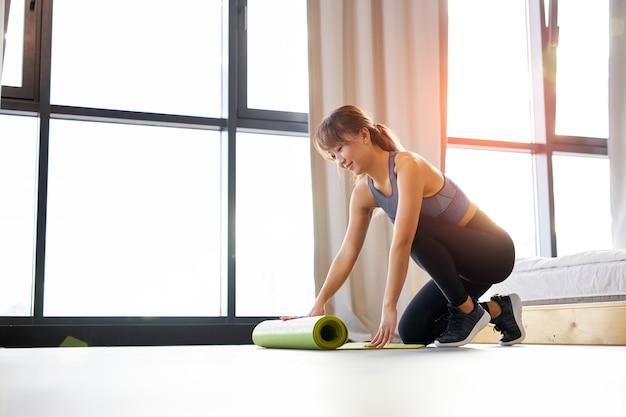 スポーツウェアのアジア人女性は、明るい部屋で、運動前の朝に床にヨガマットを広げます。健康的なライフスタイルとボディケアの概念 Premium写真