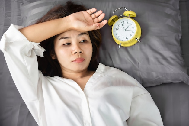 Asian woman insomnia overthinking in bed with alarm clock Premium Photo