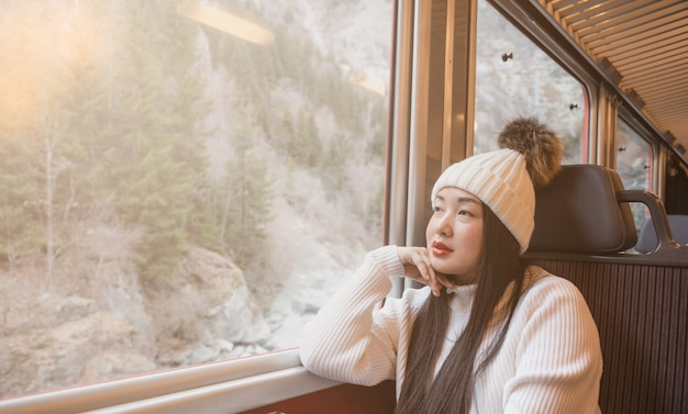 Asian woman is  looking view natural from the window on the train Premium Photo