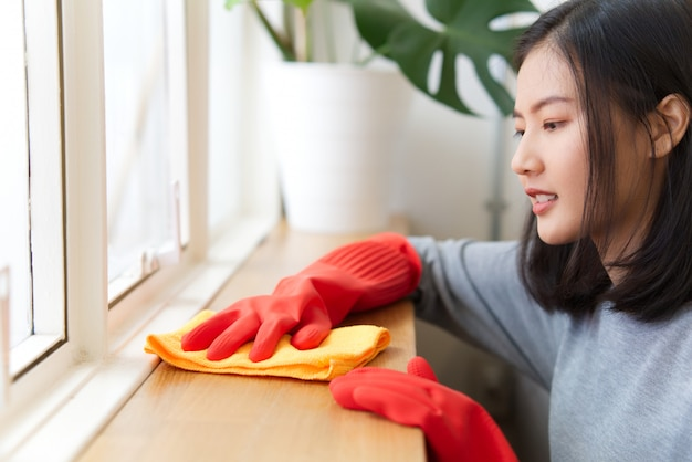 Asian woman is using a cloth wiping out dust on the wooden counter. Premium Photo