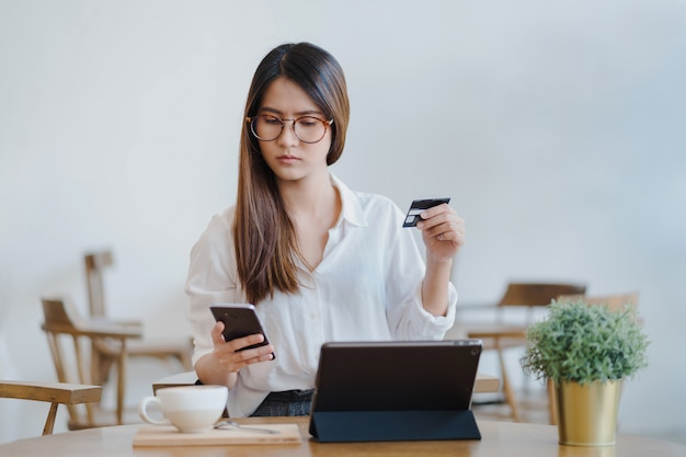 Asian woman is using tablet for shopping and paying online Premium Photo