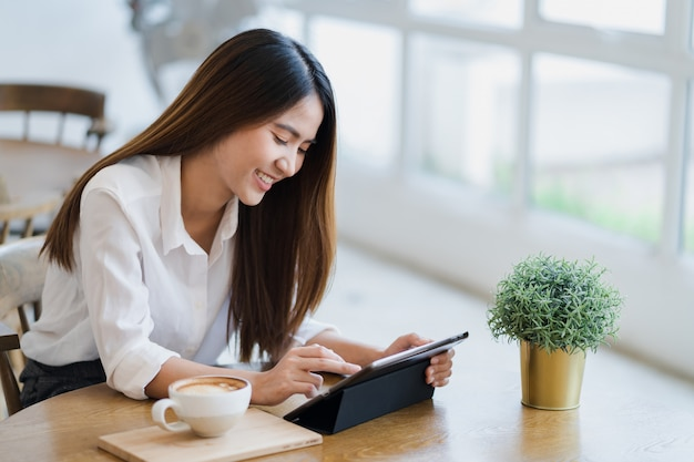 Asian woman is using tablet with smile face Premium Photo