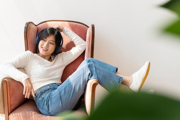 빨간 소파에서 음악을 듣고 아시아 여자 무료 사진