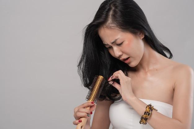 Азиатская женщина длинные волосы с расческой и проблемные волосы на сером фоне Premium Фотографии