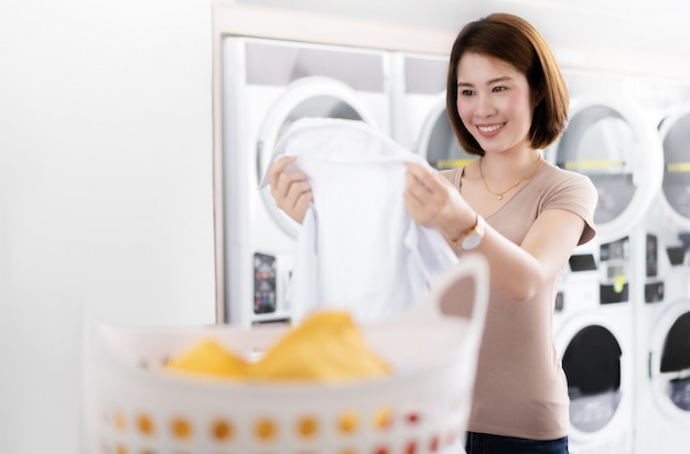 Asian woman looking her shirt the laundry store Premium Photo