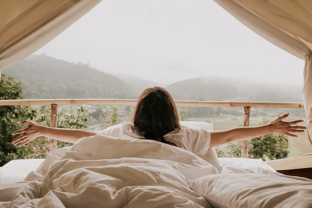 Asian woman looking at mountain view from tent in sunset time Premium Photo