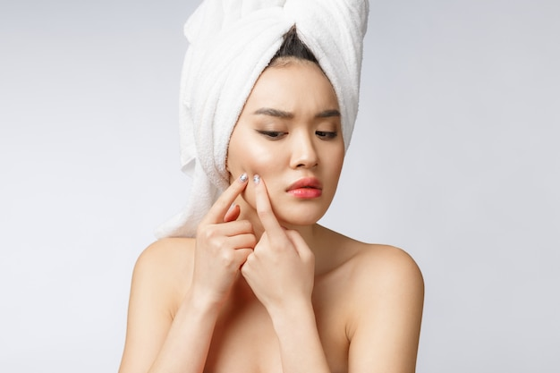 Asian woman looking at pimple on face. young woman try to remove her pimple Premium Photo