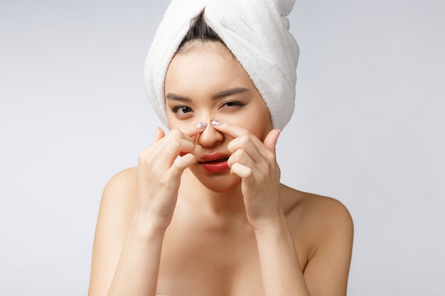 Asian woman looking at pimple on face. young woman try to remove ...