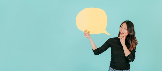Asian woman looking at speech bubble Free Photo