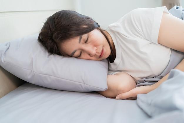 ベッドの上の白い枕で眠っているアジアの女性 Premium写真