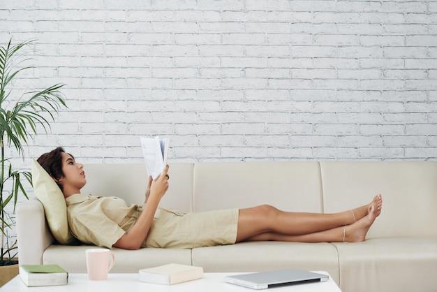 Donna asiatica che si trova sullo strato a casa e sul libro di lettura Foto Gratuite