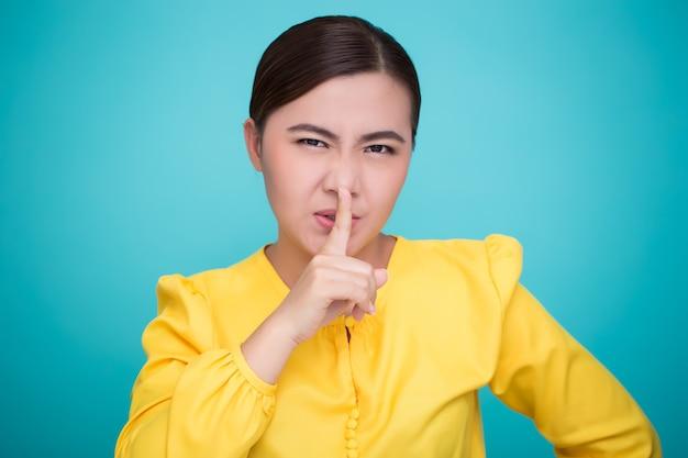 アジアの女性は静かなサインを作る Premium写真