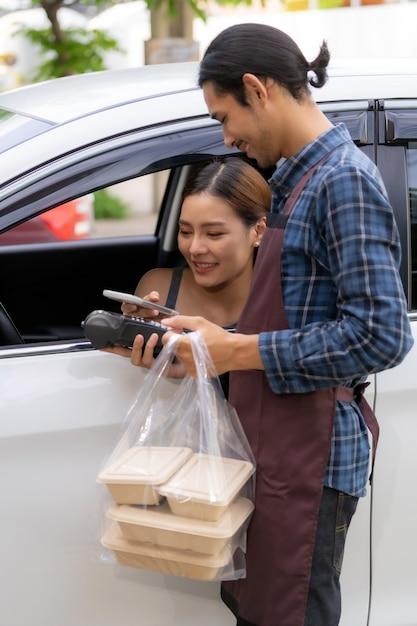 Азиатская женщина делает бесконтактный платеж с помощью кредитной карты для вывоза через еду Premium Фотографии