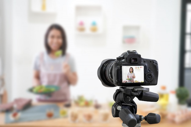 Asian woman making a vlog video digital camera for her blog cooking in the kitchen room Premium Photo