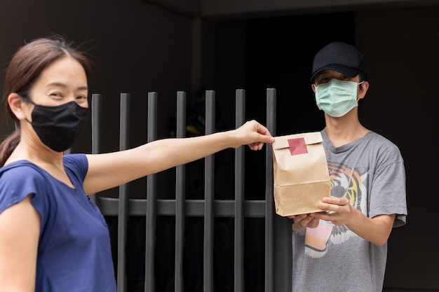 Asian woman and men wearing protective mask brown bag Premium Photo