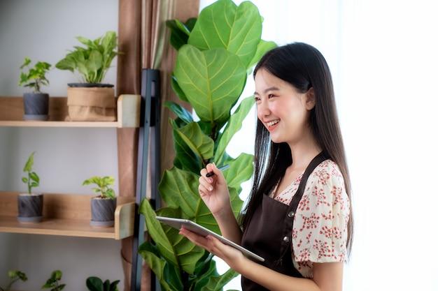 アジアの女性ousコンピュータータブレット彼女のホームオフィスで彼女の顧客からオンライン注文を受け取る、この画像はsme、ビジネス、植物、仕事、およびスタートアップのコンセプトに使用できます。 Premium写真