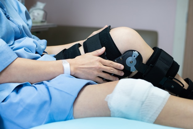 Asian woman patient with bandage compression knee brace support injury on the bed in nursing hospital.healthcare and medical support. Premium Photo