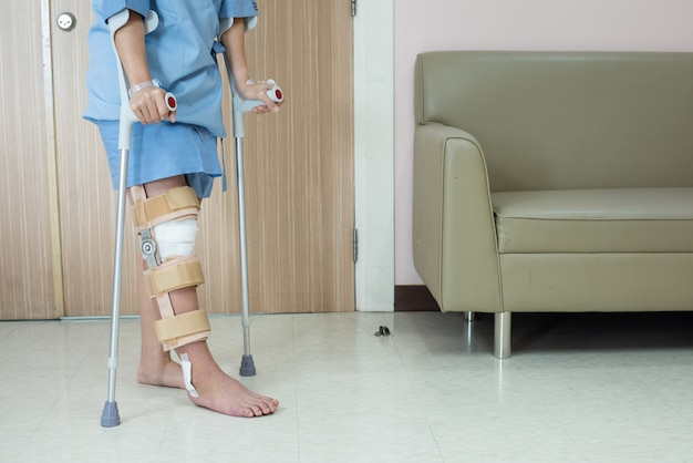 Asian woman patient with knee brace with walking stick and knee braces support in hospital ward after ligament surgery. Premium Photo