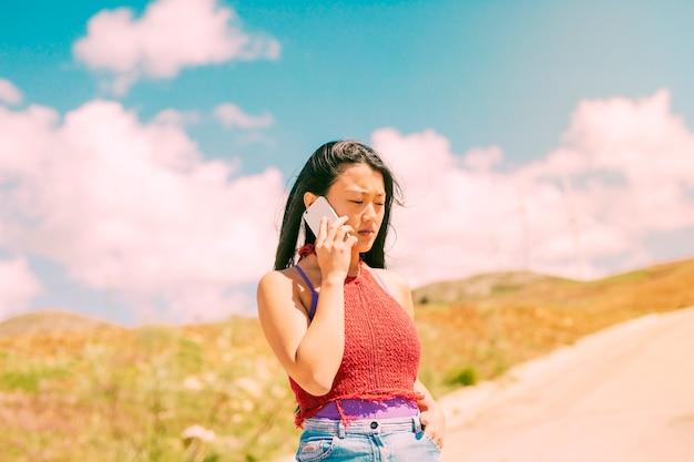 Asian woman phoning walking in countryside Free Photo