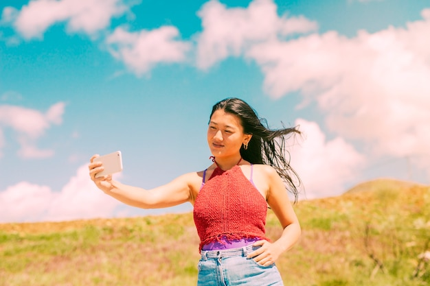 Asian woman photographing in field Free Photo