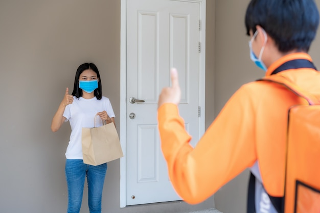 Asian woman pick up delivery food bag from door knob and thumb up form contactless or contact free from delivery rider with bicycle in front house for social distancing for infection risk. coronavirus concept Premium Photo