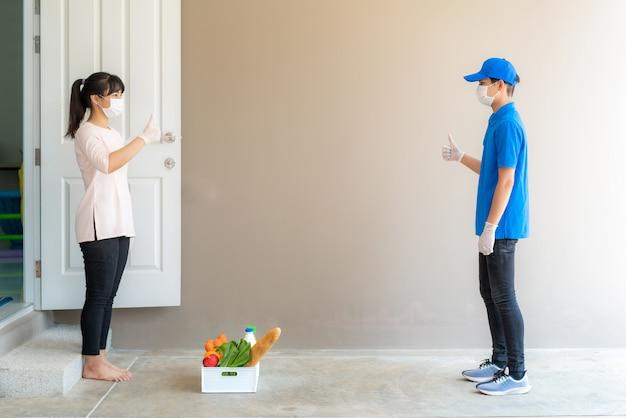 Азиатская женщина берет коробку с продуктами, фруктами, овощами и напитками и показывает палец вверх бесконтактно или без контакта с доставщиком в переднем доме для социального дистанцирования от риска заражения. Premium Фотографии
