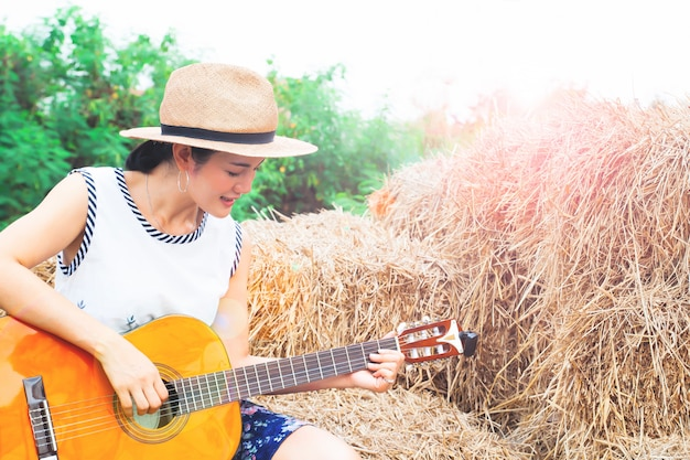 Asian woman playing guitar sitting on straw. happy woman Premium Photo