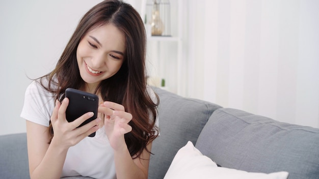 Asian woman playing smartphone while lying on home sofa in her living room. Free Photo