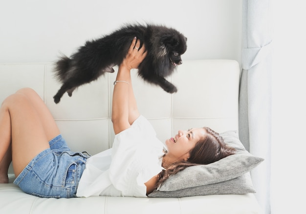 Asian woman playing with little dog black color in living room lifestyle  girl with pet | Premium Photo