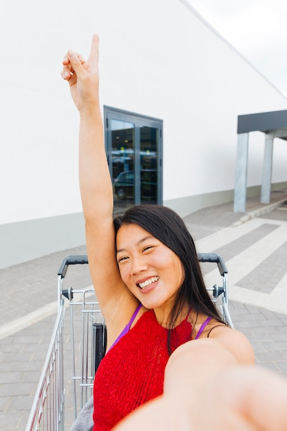 Asian woman posing and taking selfie in shopping trolley Free Photo