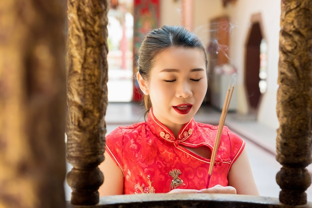Asian woman praying with incense sticks in chinese temple