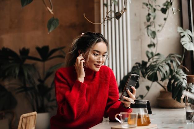 La donna asiatica mette sull'auricolare senza fili e tiene lo smartphone Foto Gratuite